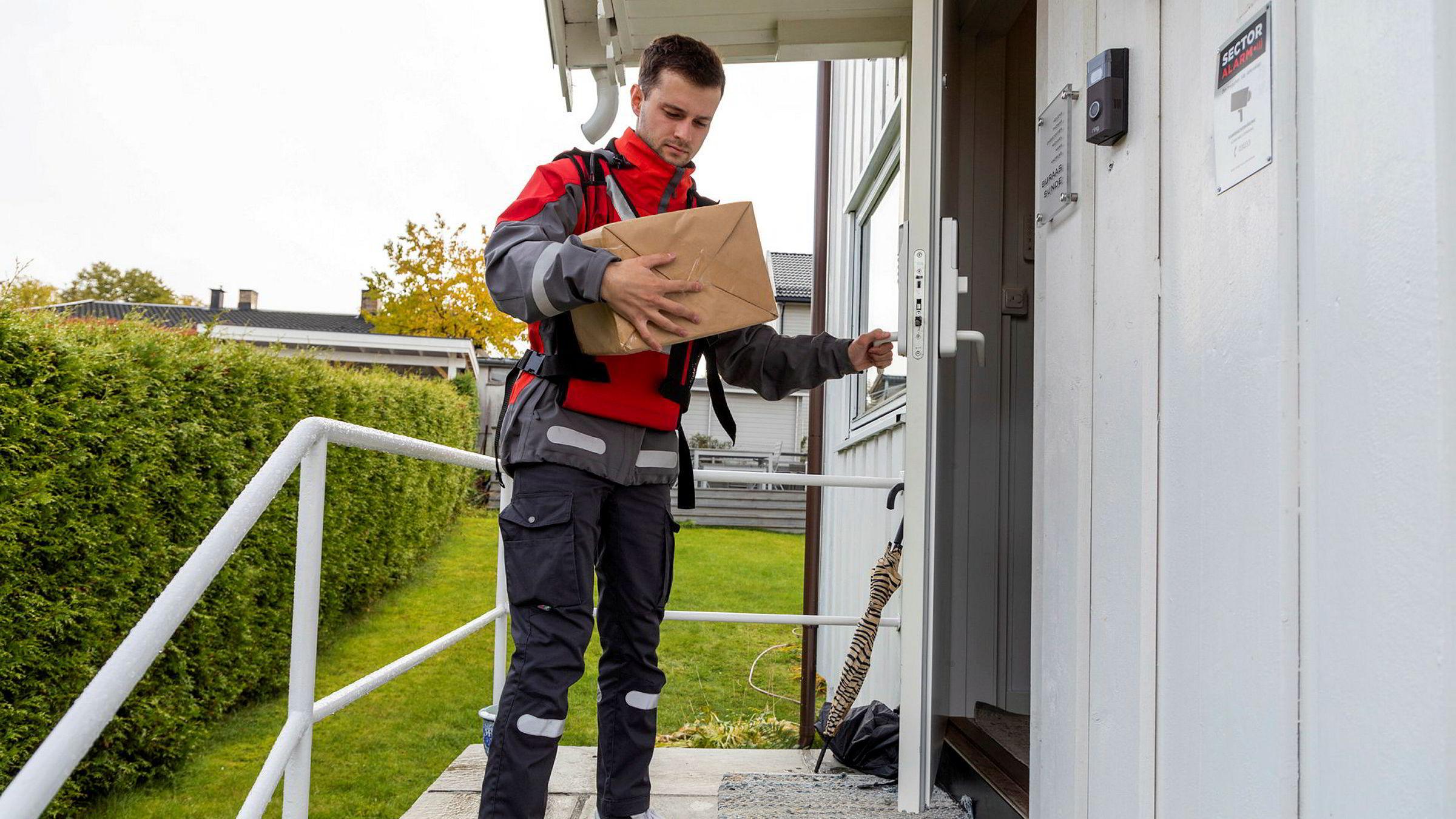 «Innafor» er navnet på en ny tjeneste og app som gjør det mulig for privatpersoner å få levert pakker inn i gangen. Her leverer postbud Pål Gunnar Molland en pakke innenfor døren til kunden.