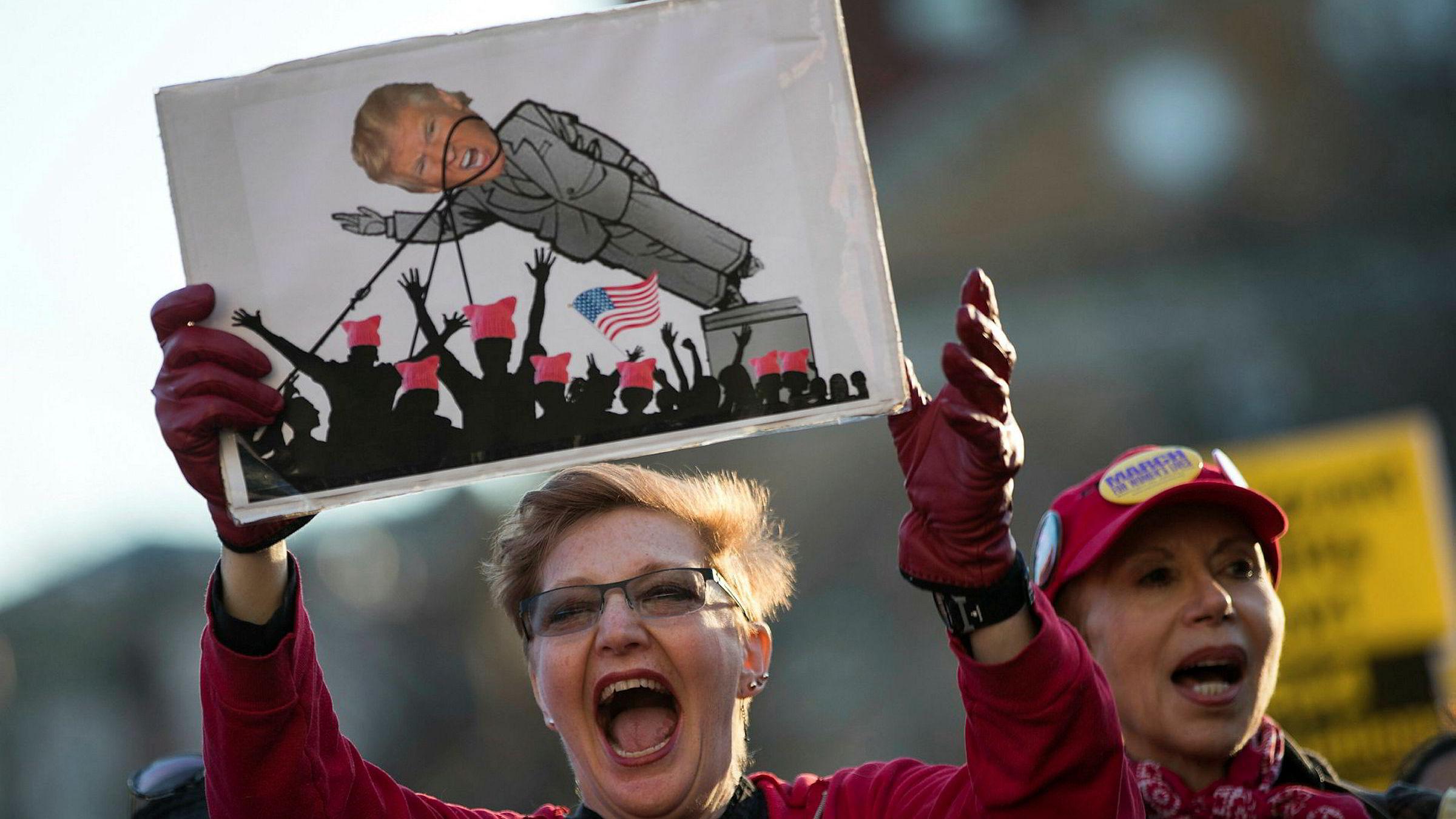 To av tre amerikanere mener det er mer hat i USA etter at Donald Trump overtok for Barack Obama. På bildet to kvinner under en demonstrasjon mot Trump i Washington på kvinnedagen onsdag.