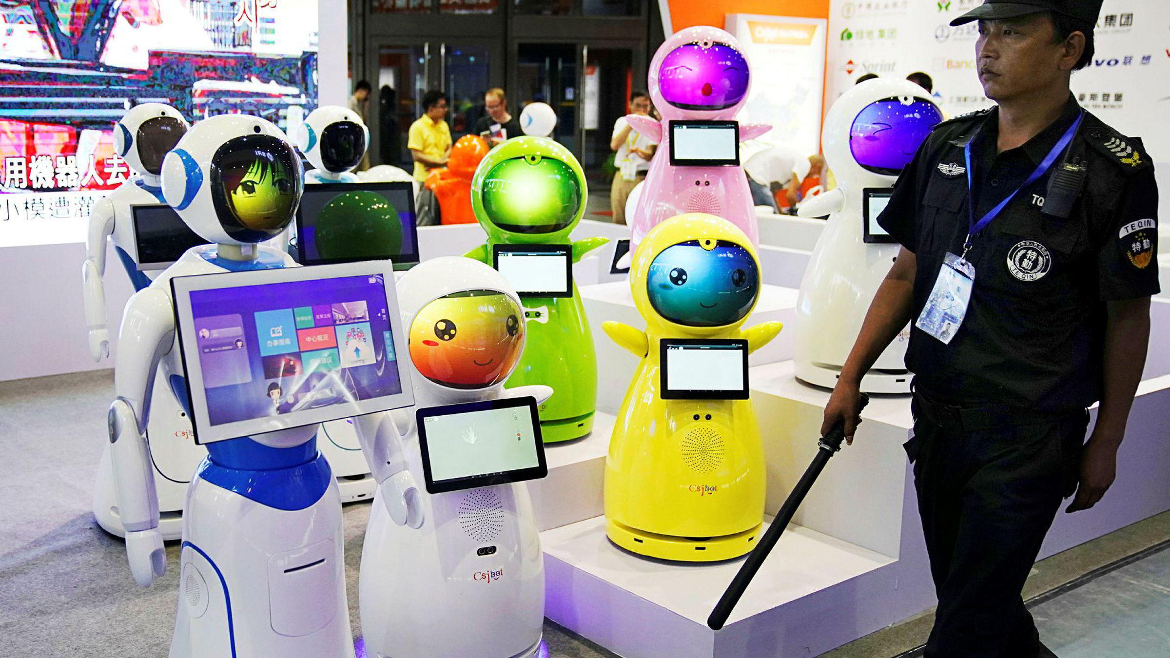 Kina satser for fullt på kunstig intelligens. På bildet passerer en sikkerhetsvakt roboter på China International Robot Show i Shanghai tidligere i juli.