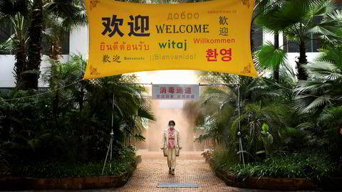 Det siste døgnet er antall smittede fra koronaviruset økt med en tredjedel, ifølge offisielle kinesiske statistikker. En ansatt ved et selskap i millionbyen Chongqing med munnbind går gjennom en enhet som sprøyter desinfeksjonsmiddel ved kontorinngangen.