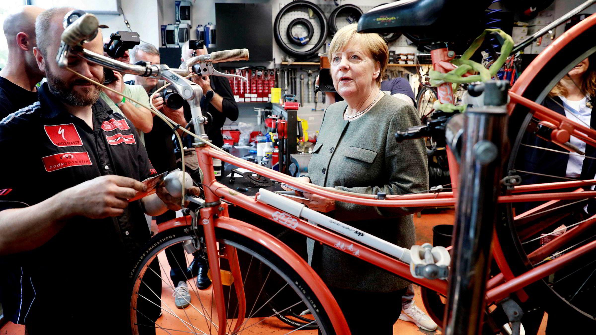Forbundskansler Angela Merkel i en sykkelbutikk i Berlin i august. Det kan bli flere av dem på veiene om et dieselforbud kommer på plass.