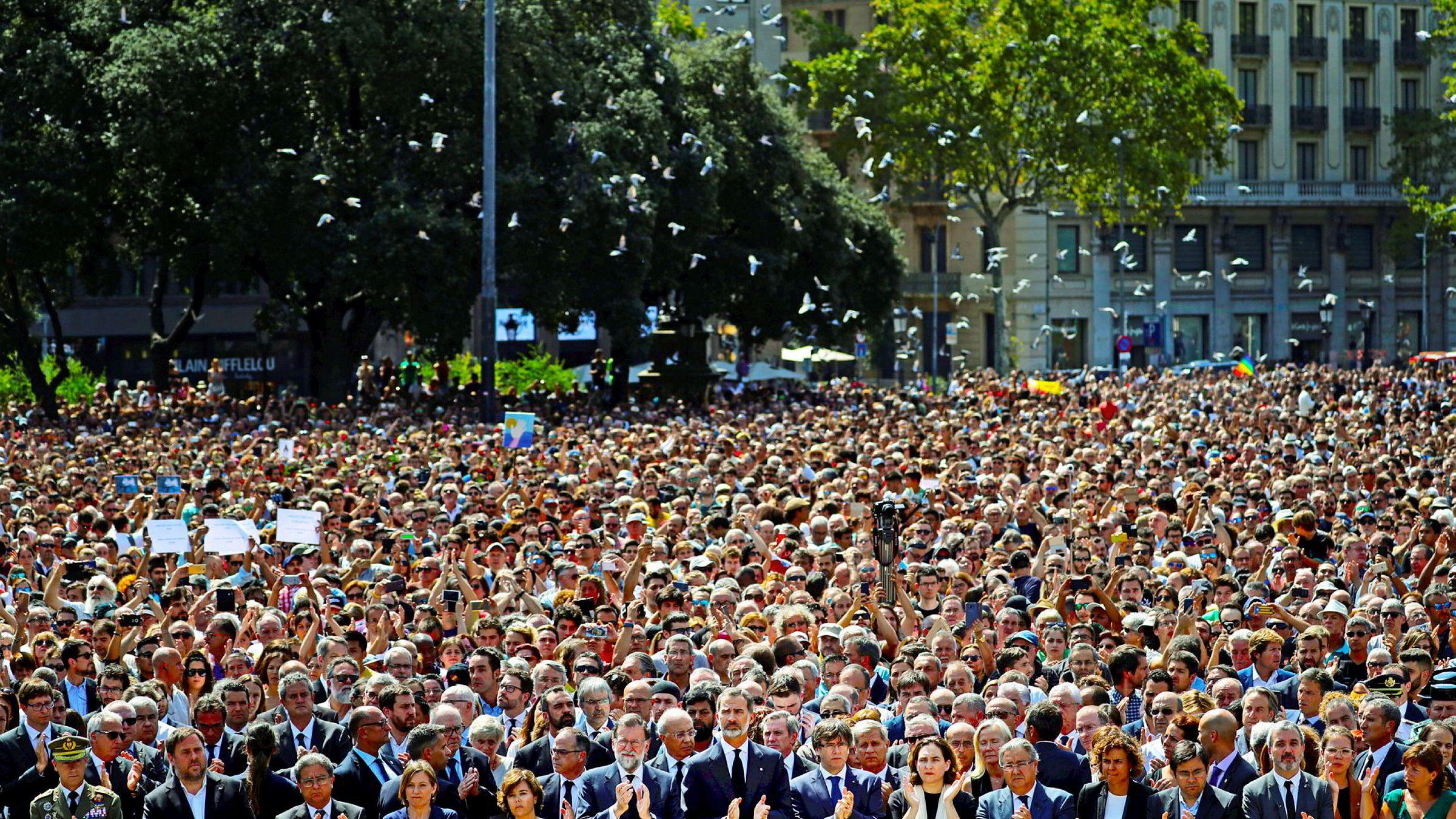 Kong Felipe av Spania (i midten av bildet foran) og statsminister Mariano Rajoy (til venstre for kongen) holdt ett minutts stillhet mens duene fløy over Placa de Catalunya i Barcelona, dagen etter at terroren drepte 14 mennesker i paradegaten La Rambla.