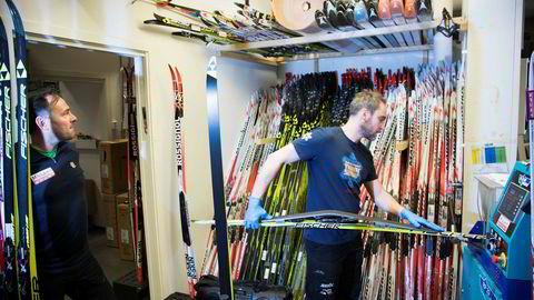 Butikksjef Ragnvald Reed i Milsluker'n ser på lageret av usolgte ski bak Øyvind Sandbakken som steinsliper ski til årets siste renn. - Vi har ikke flere ski på lager etter denne sesongen enn vi vanligvis har, sier han.