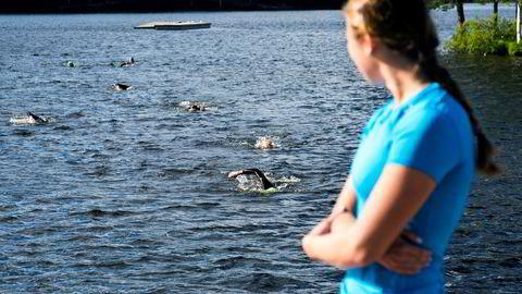 Svømmetrener Emma Augustsson ser ut over Sognsvann og triatletene som svømmer mot henne.
