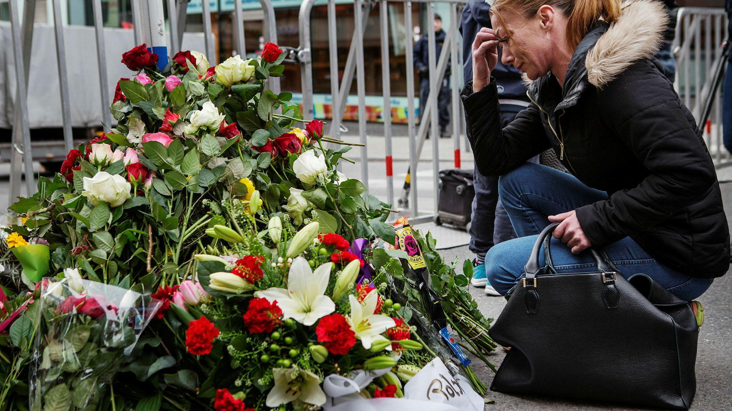 Erika Angermund legger ned blomster foran sperringen like ved Åhléns-varehuset i Drottninggatan. Hun har tatt turen til byen med familien for å ta del i sorgen.