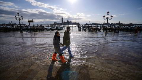 Et par vasser forbi gondoler fortøyd ved det oversvømte Riva degli Schiavoni-vollen. Strandede gondoler og ødelagte hoteller har skapt store utfordringer for byens turistindustri.