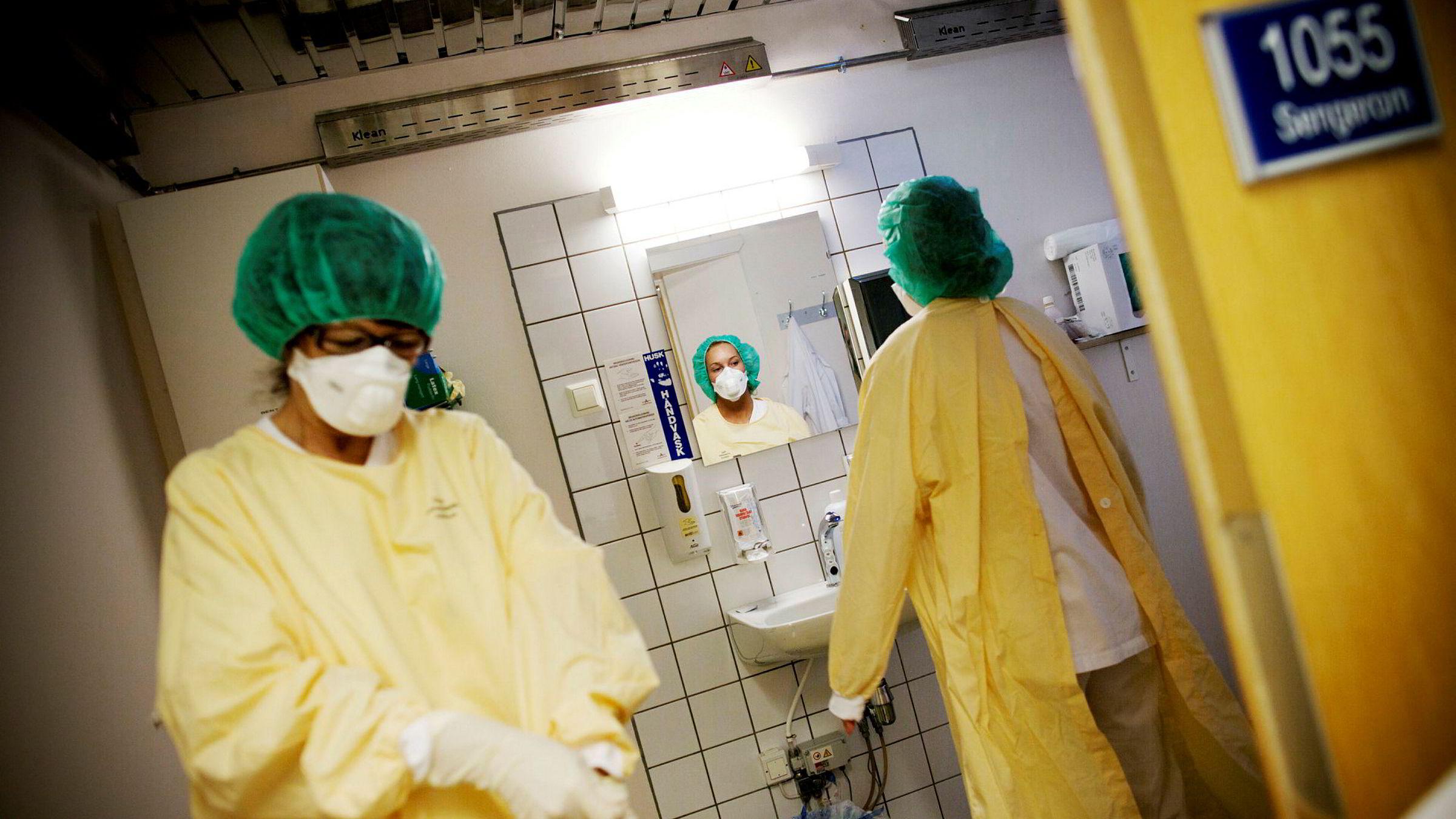 Lege Eyrund Kjetland og sykepleier Anette Schneider (ved speilet) på vei inn i et isolat på Ullevål sykehus.
