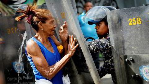 I dag dør folk av underernæring og sykdom i Venezuela. En kvinne går i protest mot opprørspolitiet på grunn av mangel på mat.
