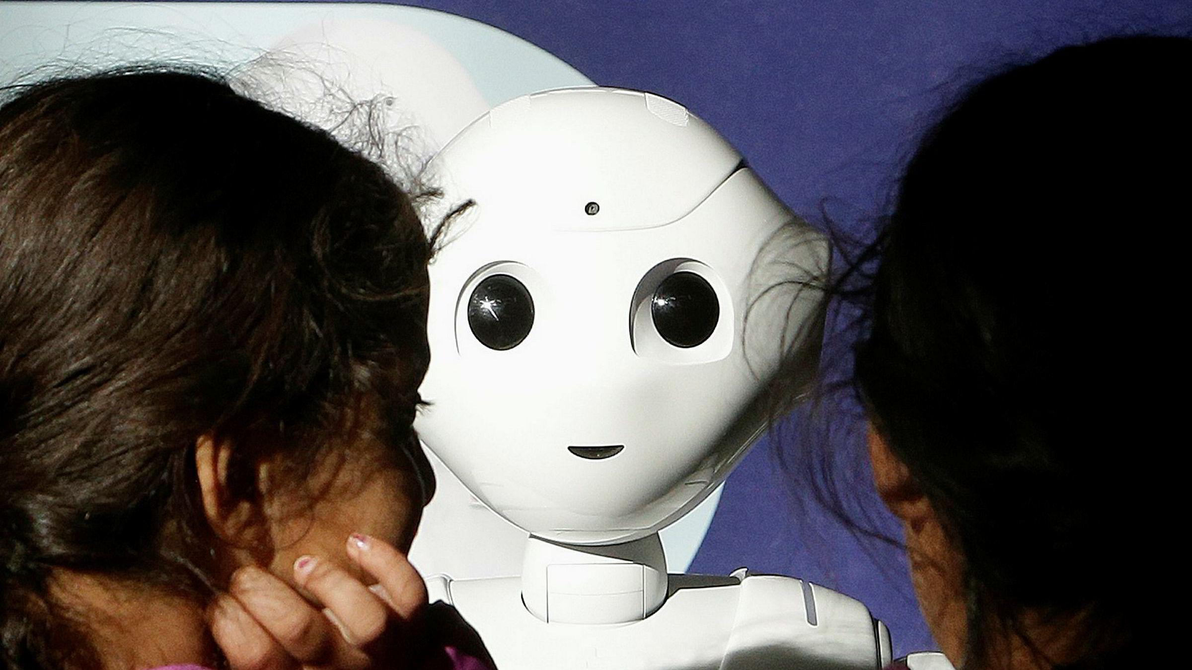 To søstre leker med roboten Pepper på et kjøpesenter i San Francisco. Dette er en av de lengst fremskredne menneskelignende robotene.