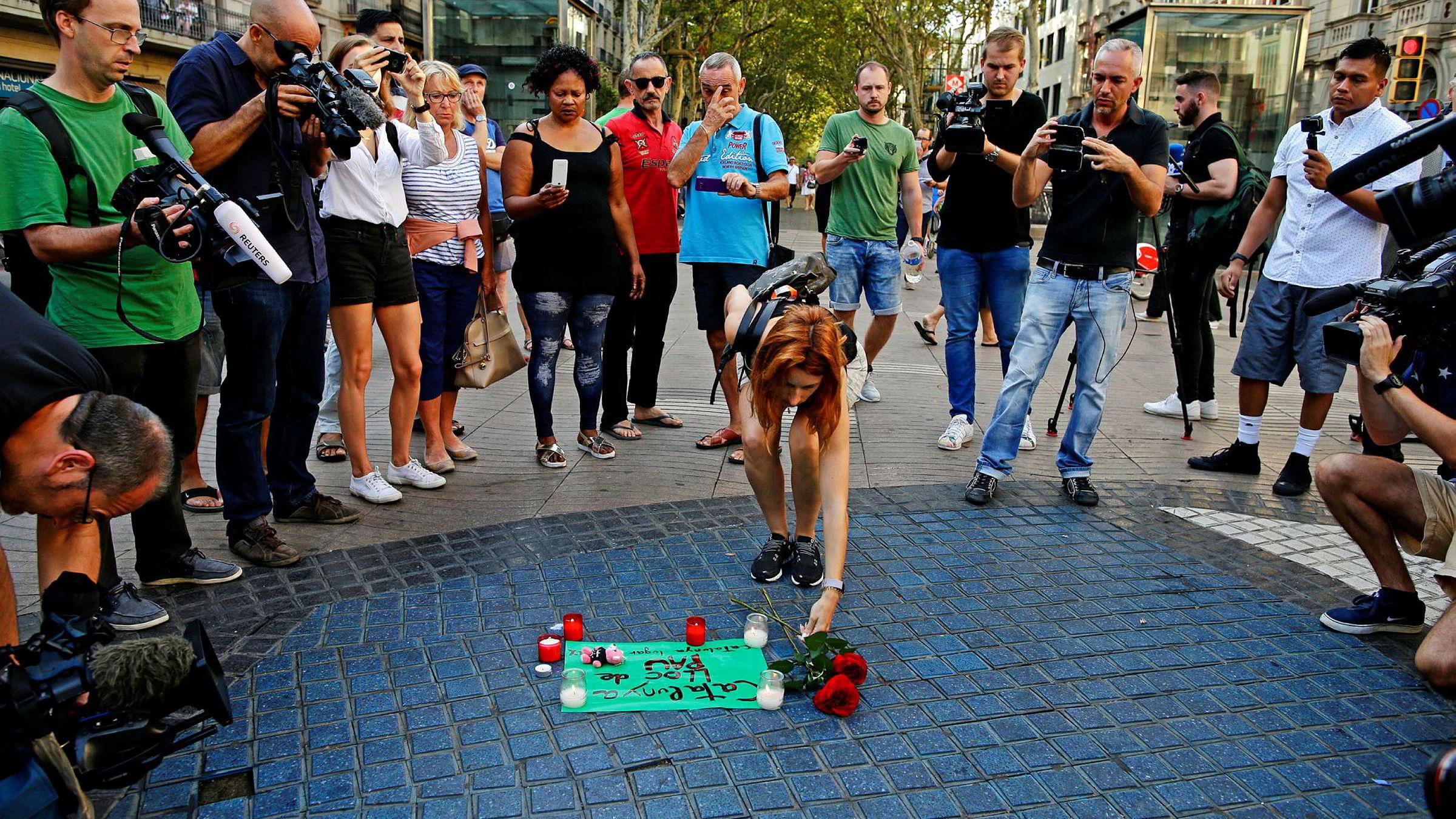 En kvinne plasserer blomster på et papir hvor det står «Catalunya – et sted for fred» på gaten La Rambla i Barcelona etter terrorangrepet.