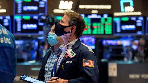 Aksjemegleren Robert Charmak, godt beskyttet med munnbind, fulgte nøye med på hvordan børsindeksene danset oppover under handelen på New York Stock Exchange fredag.