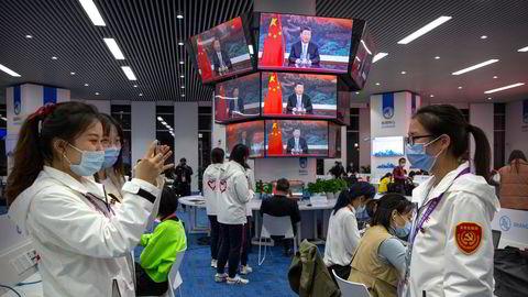 Frivillige tar bilder foran videoskjermene som viser president Xi Jinping åpne handelsmessen China International Import Expo i Shanghai i november.