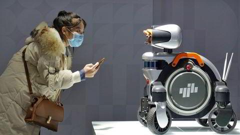 En kvinne studerer en patruljerobot på  World Industrial Design Conference i Yantai i det østlige Kina. Kinas ledelse vil ha raskere teknologisk utvikling for å øke Kinas økonomiske uavhengighet.