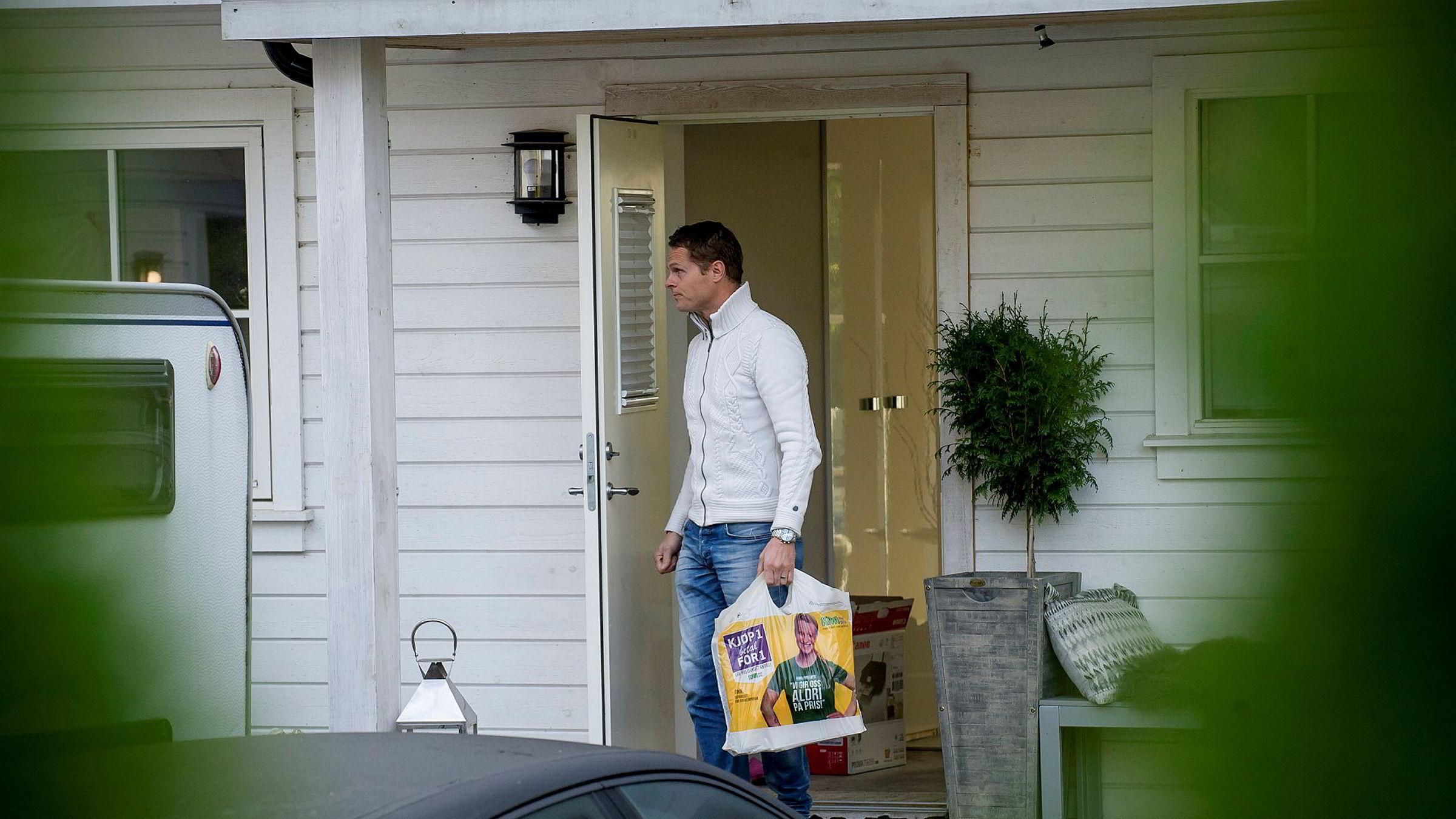 Her hjelper snekker Carl Thomas Andersson til med å bære ut beslaglagte dokumenter i en Kiwi-pose under ransakingen av timillionersvillaen.