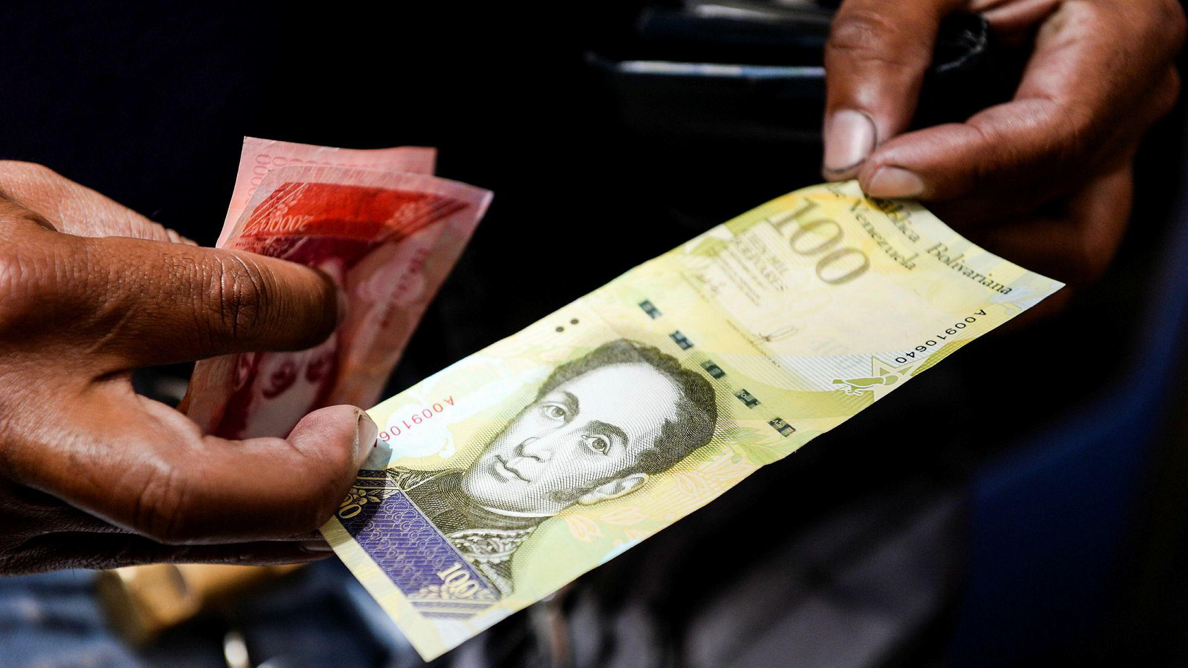 Venezuela vil trolig havne i mislighold av landets enorme statsgjeld. På bildet viser en mann frem landets nye 100.000-Bolivar-seddel. i det offisielle markedet er den verdt 29,89 dollar, men på svartebørs kan man kjøpe den for to dollar.