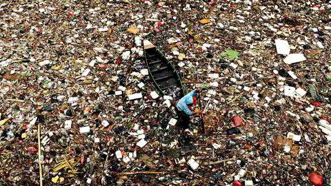 Plasthav. En mann samler plast for gjenvinning i en elv av søppel i nærheten av demningen i Pluit, Jakarta. Bildet er tatt i 2009.