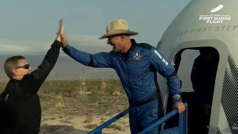 Jeff Bezos stiger ut av romkapselen og blir møtt med en high-five etter den vellykkede oppskytningen.