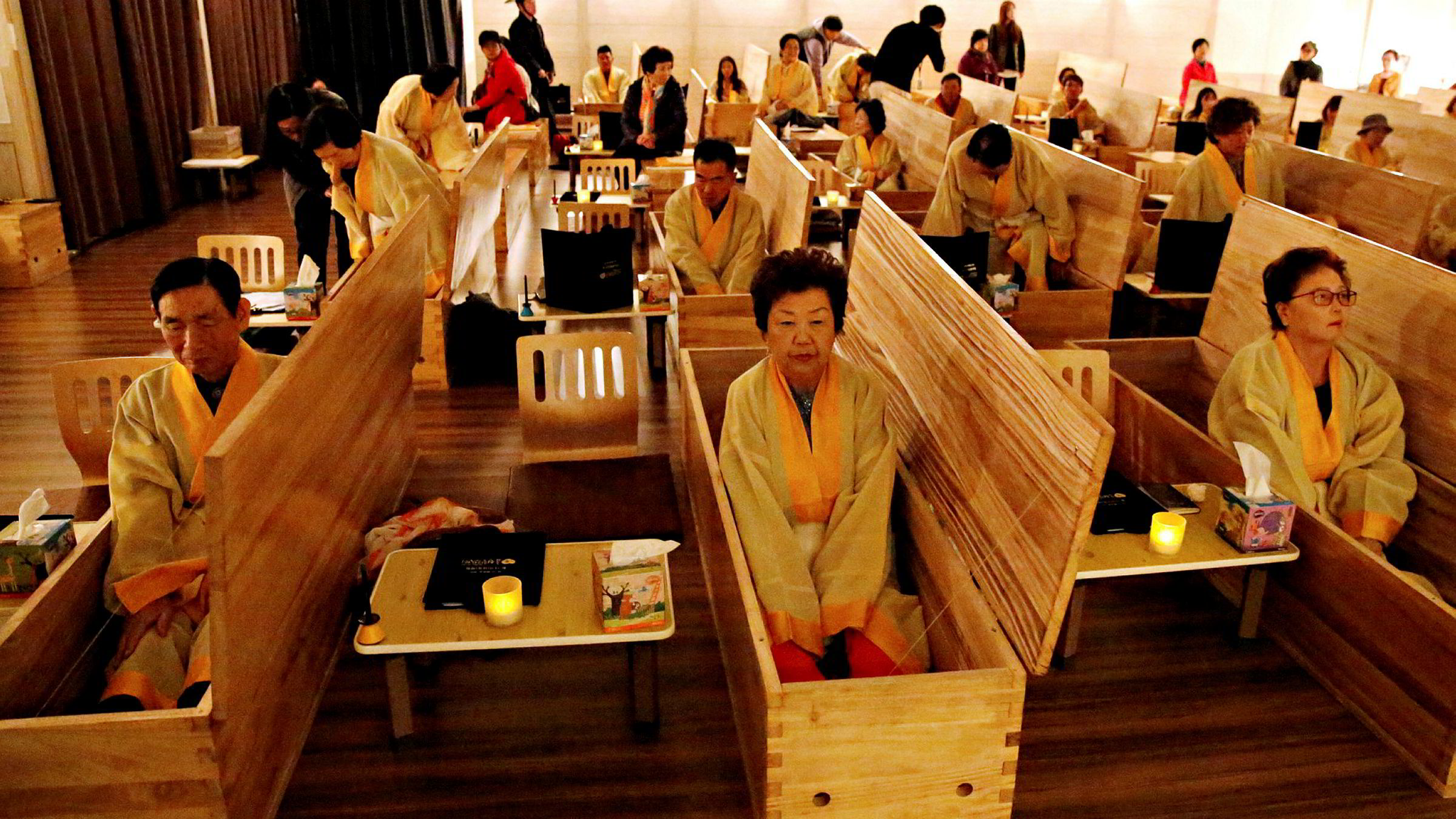 Participants sit inside coffins during a «living funeral» event as part of a «dying well» programme, in Seoul, South Korea, October 31, 2019. Picture taken on October 31, 2019. REUTERS/Heo Ran TPX IMAGES OF THE DAY ---