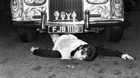 Made in England. Uansett hvor radikal han var, måtte også John Lennon, som det britiske ikon han var, ha sin egen, fornemme Rolls-Royce. Her later han som om han blir overkjørt av den.
