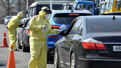 Medisinpersonell med smittevernutstyr tester sjåfører med mistenkelige symptomer for koronaviruset i Goyang nord for Seoul i Sør-Korea.