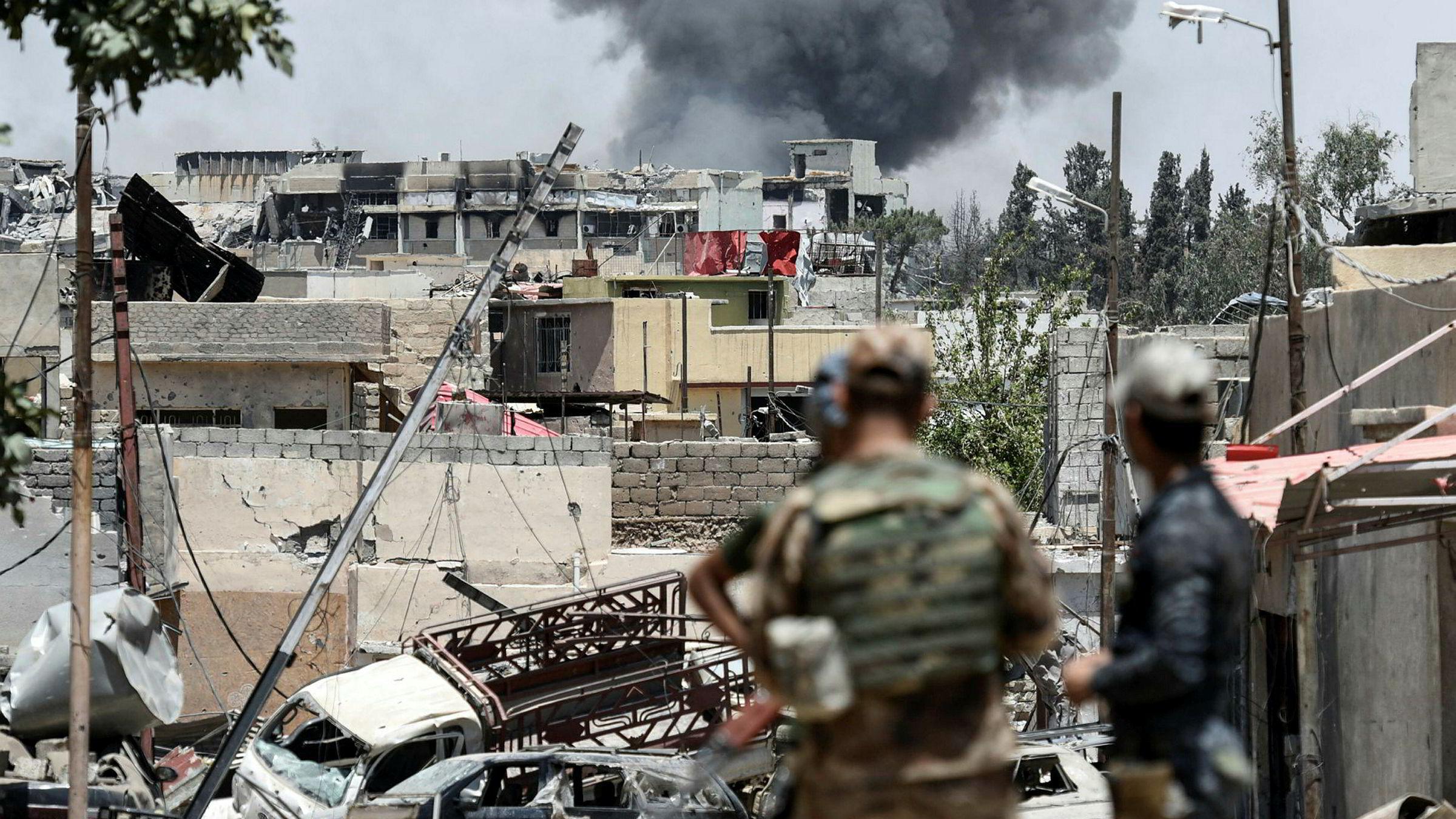 Røyk velter opp etter kamphandlinger i Mosuls vestlige Al-Shifa-distrikt 15. juni i år. Irakiske styrker kjemper for å gjennvinne kontrollen fra IS.