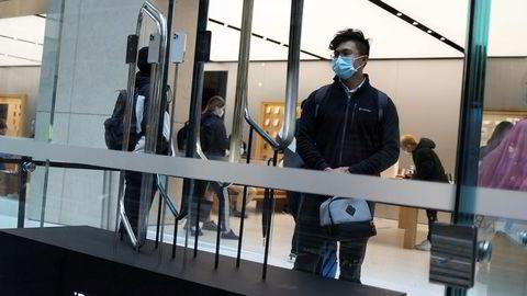 Apple har nylig lansert Iphone 12. Her kaster en kunde et etterlengtet blikk på modellen på innsiden av en Apple-butikk i New South Wales i Australia.