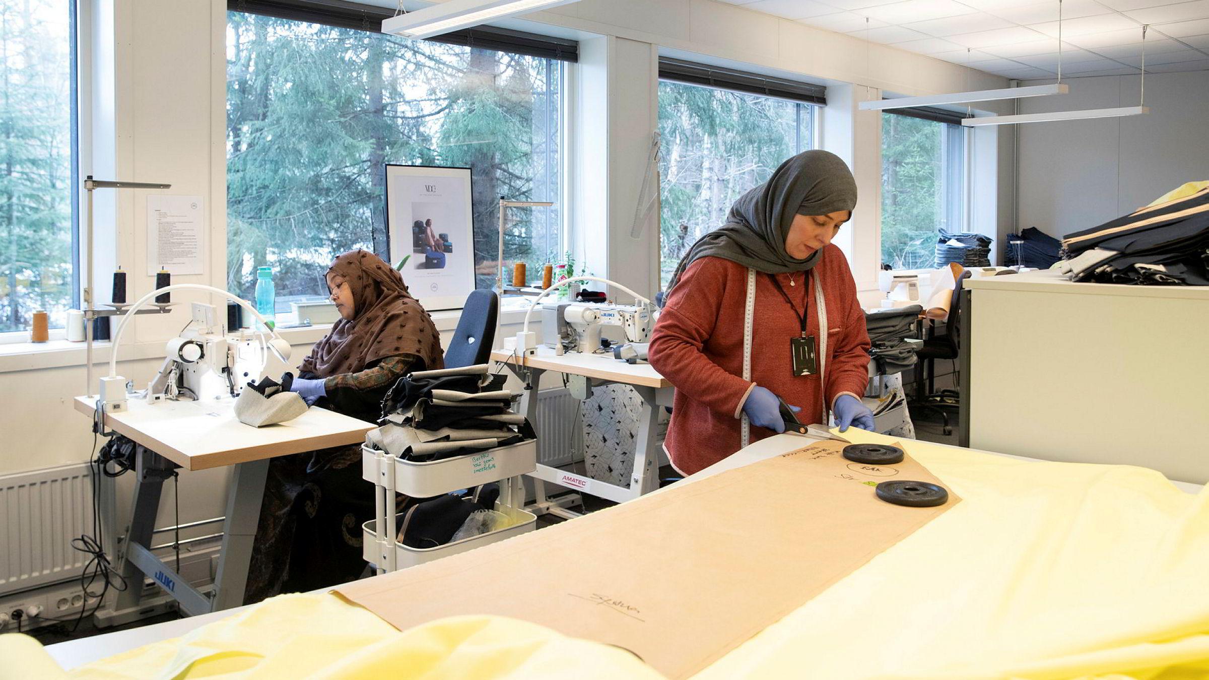 Hodan Jama Farrah (i bakgrunnen) syr og Fatima Malala klipper til bomullsstoff til en smittervernsfrakk på bedriften Sisters in Business i Asker. Sisters in Business er et sosialt entreprenørskap som rekrutterer og sysselsetter innvandrerkvinner.