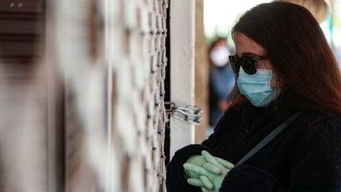 En kvinne med ansiktsmaske venter på å slippe inn på shoppingsenteret Apumanque i Santiago i Chile i slutten av april. Først nå begynner smittetallene for alvor å ta av i landet, og kirkegårdsarbeidere forbereder seg for å ikke risikere at døde blir liggende i massegraver eller på vent i likbiler