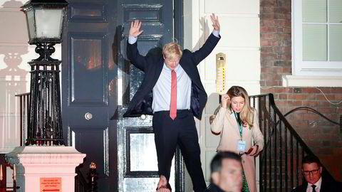 Statsminister Boris Johnson og kjæresten Carrie Symonds var i god stemning da de i natt forlot Det konservative partiets valgvake i London. Hunden Dilyn var også med på festen.