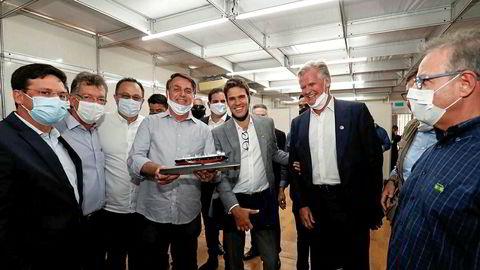 Her står konsernsjef Eduardo Antonello (i midten) i Hygo Energy Transition (tidligere Golar Power) mellom styreleder Tor Olav Trøim i Hygo (til høyre) og Brasils president Jair Bolsonaro (til venstre). Her fra gassfabrikken Sergipe i Brasil hvor Bolsonaro var på besøk i august år.