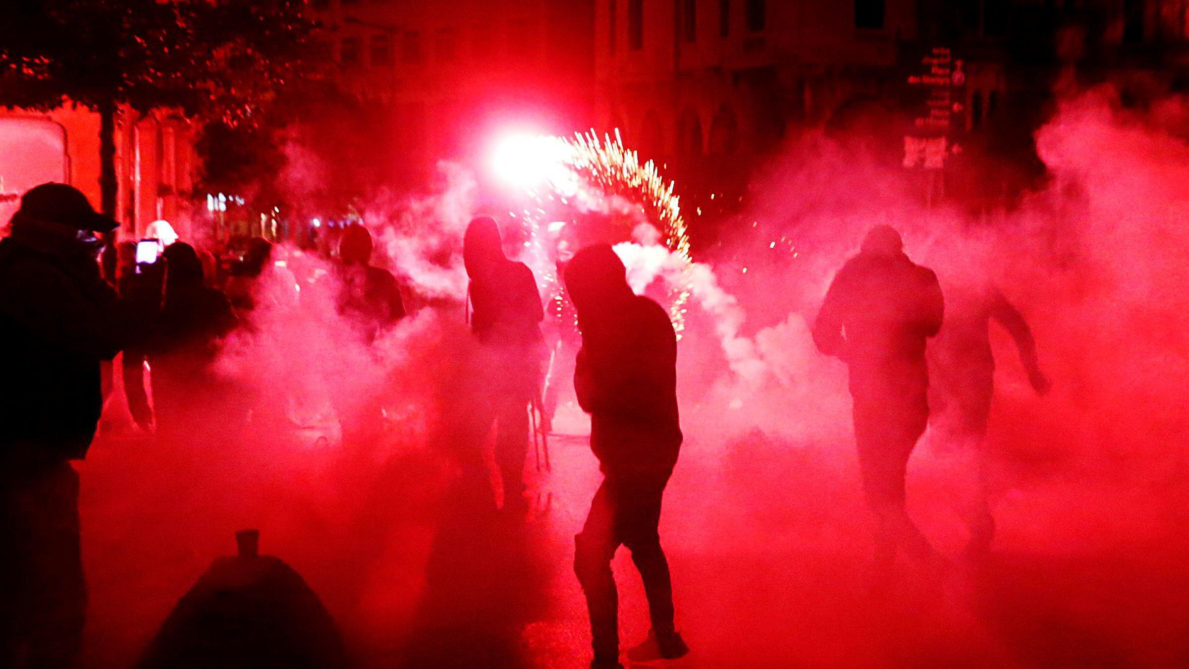 Demonstranter dekket i en sky av tåregass kaster brennende gjenstander mot det lokale politiet. Sentrum av Beirut var preget av voldsomme demonstrasjoner natt til lørdag.